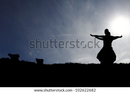 Silhouette of Indian classical duet dancers in a rural surrounding of lamb pasture in the countryside against a surreal dramatic cloudy blue sky. - stock photo