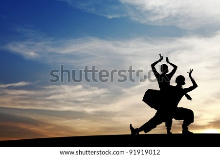Silhouette of Indian cultural duet dancers posing on a hill against a surreal dramatic sunset sky. - stock photo