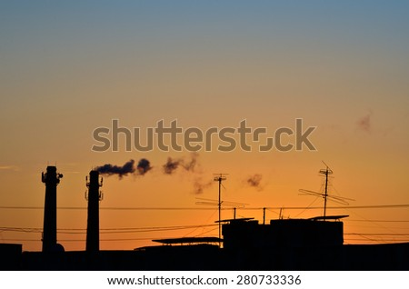 Silhouette of industrial production, polluting the atmosphere - stock photo