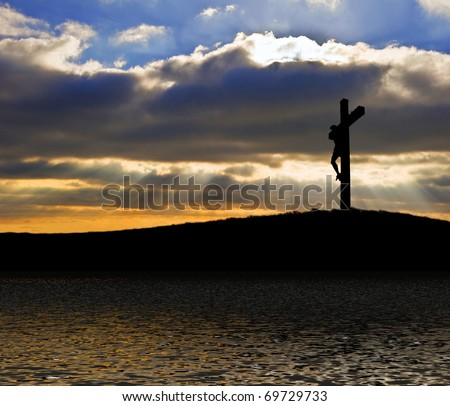 Silhouette of Jesus Christ crucifixion on cross on Good Friday Easter reflected in lake water - stock photo