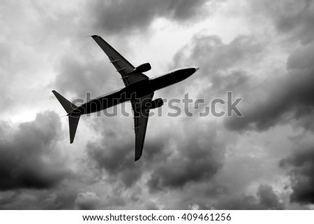 Silhouette of jet in dark cloudy sky - stock photo