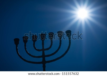 Silhouette of jewish lightstand called menorah. Symbol of winter light festival called Hanuka (Hanukka, Chanukkah). / Menorah with a star. - stock photo