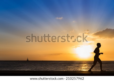 Silhouette of jogging man at the beach with sunset background