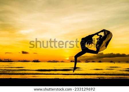 silhouette of jumping girl on tropical sunset sea and sky background - stock photo