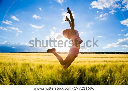 silhouette of jumping kid in the wheat field - stock photo
