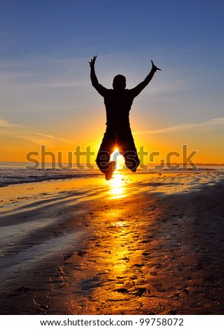 silhouette of jumping man against sunset - stock photo