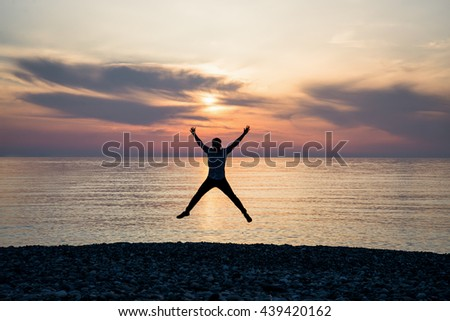 Silhouette of jumping man on sunrise background