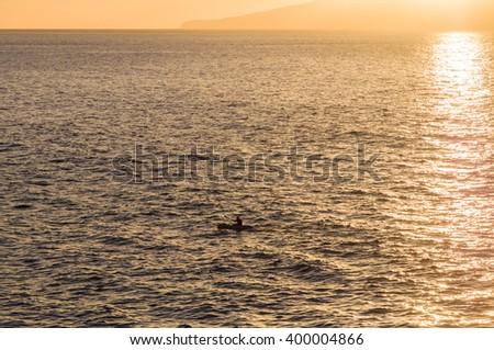 Silhouette of kayak oar in sunset light, sun sparkles on water - stock photo