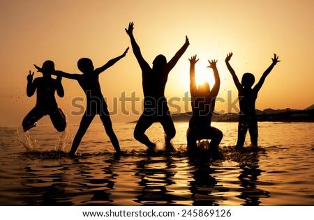 Silhouette of kids jumping on the beach on beautiful summer sunset - stock photo