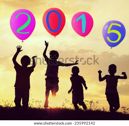 Silhouette of kids with balloons running and jumping on the summer sunset meadow for happy new 2015 year - stock photo