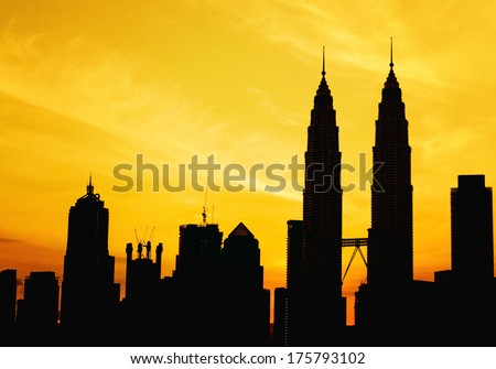 silhouette of KLCC and other skyscraper tower during golden sunrise - stock photo