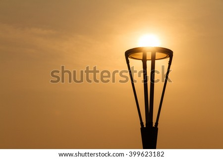 Silhouette of lamp pole on sun and sky background.