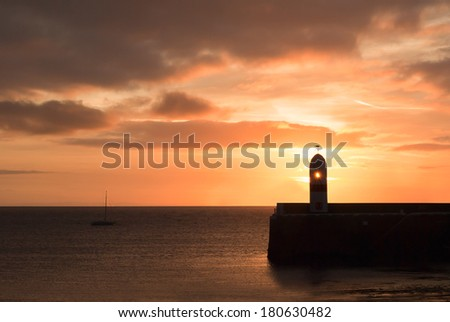 Silhouette of Lighthouse on breakwater wall with calm sea during sunrise.  Tranquil scene on Isle of Man - stock photo