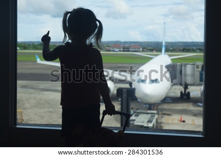 Silhouette of little baby girl waiting boarding to her flight in airport transit hall and looking at airplane parking near departure gate. Travelling by air with child during family summer vacation  - stock photo