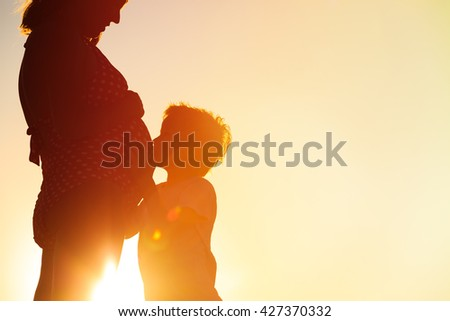 Silhouette of little boy hugging pregnant mother tummy at beach - stock photo