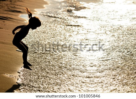 Silhouette of little girl jumping on the beach - stock photo