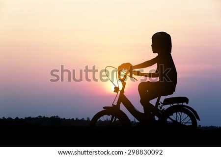 Silhouette of little girl on a bicycle at sunset