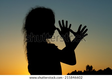 Silhouette of little girl who teases, putting fingers to nose. - stock photo