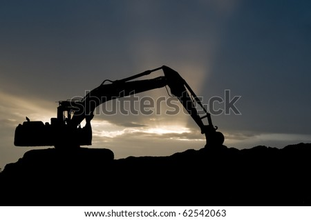 silhouette of loader excavator scoop shovel over scenic sunset - stock photo