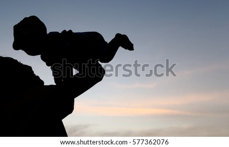 Silhouette of long hair girl raises her boy in the air with evening sky background.