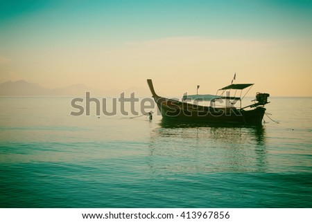 Silhouette of long tail boat in mystical sunset.Grain and colour styling applied - stock photo