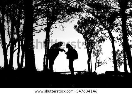 silhouette of love couple in trees border, back and white tone.