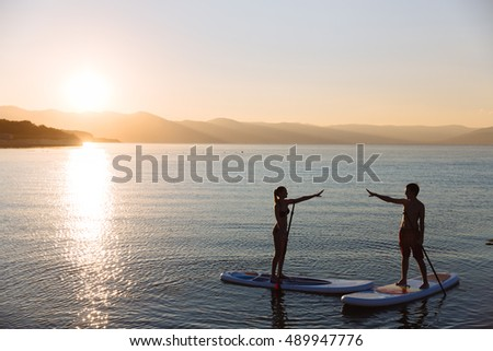 Silhouette of male and female on sup surf pull hands together at the ocean. Concept lifestyle, sport, love
