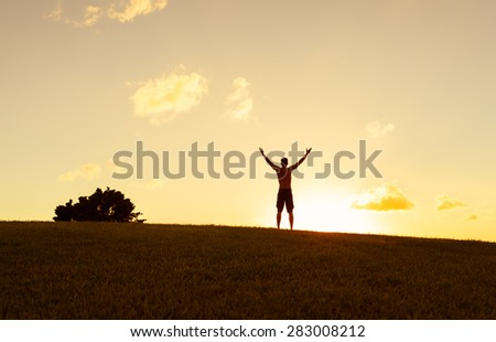 Silhouette of male celebrating during a beautiful sunset.    - stock photo