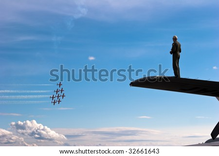 Silhouette of male pilot standing on airplane wing watching jet formation fly by against big blue sky