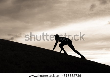 Silhouette of male runner stretching.  - stock photo