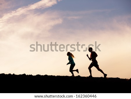 Silhouette of man and woman running jogging together into sunset, Wellness fitness concept - stock photo
