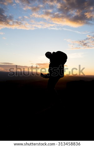 silhouette of man at sunset - stock photo