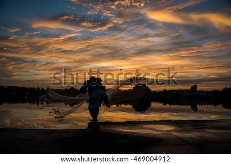 silhouette of man casting a fishing net at sunrise with beautiful orange clouds in background