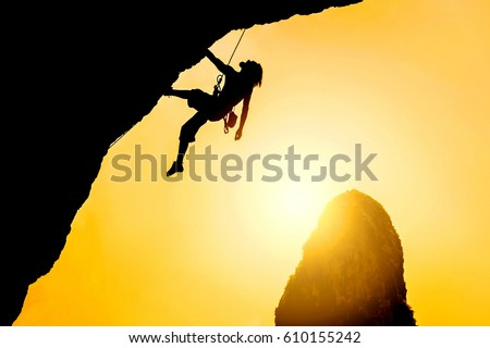 Silhouette of man climbing at sunset. The rock climber during rock conquest. Climbing sport concept.