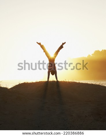 Silhouette of man doing a handstand - stock photo