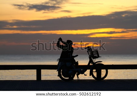 silhouette of man enjoy sunrise on the beach in the morning
