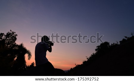 silhouette of man enjoying sunset - stock photo