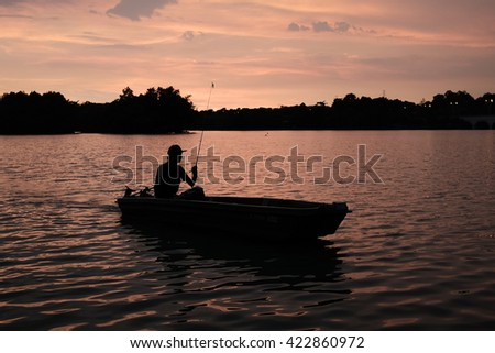 Silhouette of man fishing during sunset.