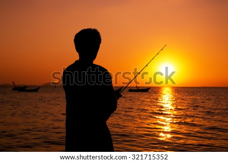 Silhouette of man fishing in a sunset