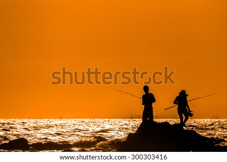 Silhouette of Man fishing on sea shore