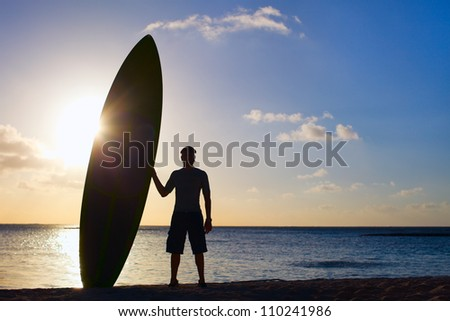 Silhouette of man holding paddle board on a beach at sunset - stock photo
