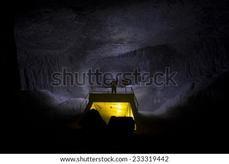 silhouette of man in a cave with yellow light painted structure - stock photo