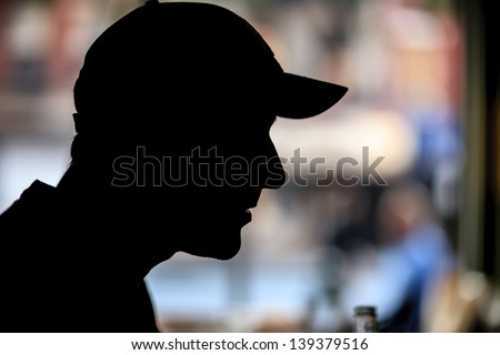 Silhouette of man in baseball cap indoors over bokeh blur background. Closeup, copyspace. - stock photo