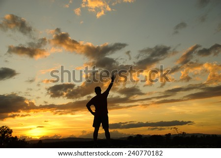 Silhouette of man in the evening watching beautiful sunset with arms raised up outstretched cheering and happy. - stock photo