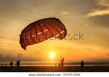 Silhouette of man is preparing para sailing at the sunset beach in Thailand - stock photo