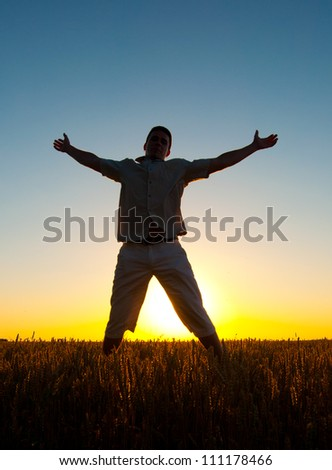 Silhouette of man jumping high in the wheat field on sunny summer day. - stock photo