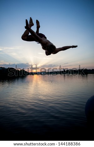 silhouette of man jumping in lake in sunset  - stock photo