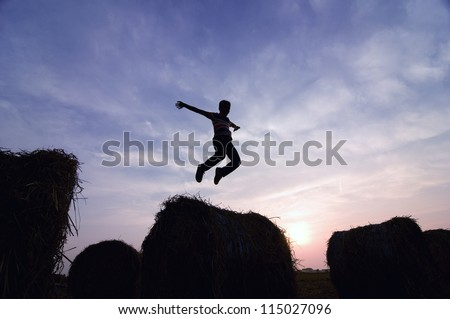 silhouette of man jumping in sunset - stock photo