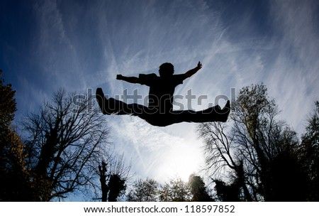 silhouette of man jumping on trampoline in sky - stock photo