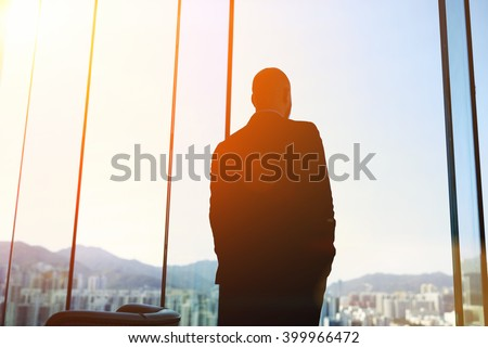 Silhouette of man managing director is examining the challenges the company after the refusal of investors in financing, while standing in evening time against office window background with copy space - stock photo